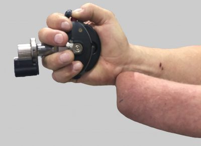 A customer with a wrist disarticulation amputation gripping the Palm Pistol®. The optional barrel extension may be used to gain additional leverage to close the action.